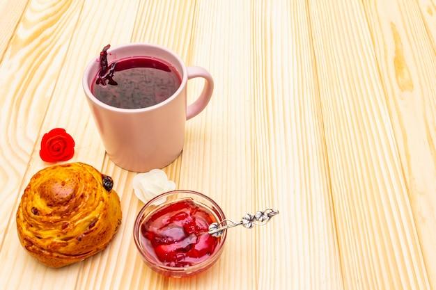 ハイビスカスの花びらからのカルカデ茶(スーダンのバラ)。穏やかなロマンチックな朝食コンセプト。パン、メレンゲ、イチゴゼリー。木製の表面にスペースをコピーします。