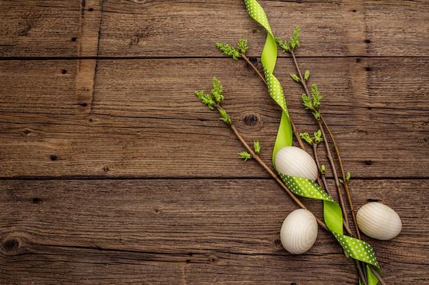 Ноль отходов пасхи концепции. весенние веточки со свежими зелеными листьями, деревянные яйца, горошек ленты. старые старинные деревянные поверхности доски