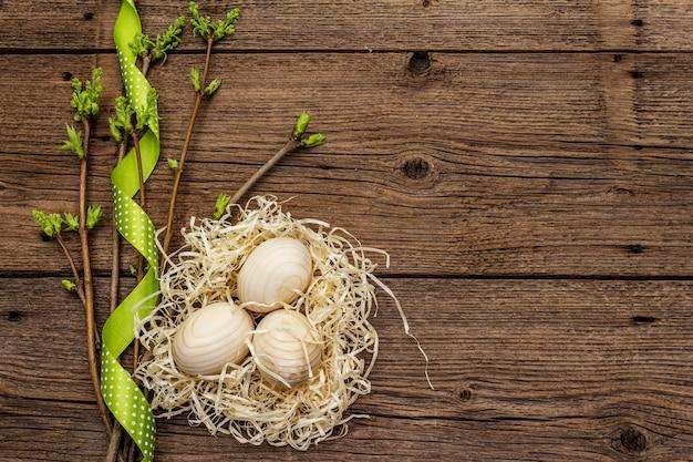 Ноль отходов пасхи концепции. весенние веточки со свежими зелеными листьями, деревянные яйца в гнезде, горошек ленты. старые старинные деревянные поверхности доски