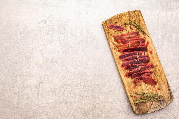 ヴィンテージの木製ボード上の乾燥ローズマリーとコショウのミックスと牛肉の乾燥テンダーロイン