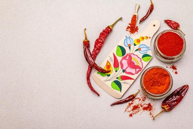 マジャールレッドの甘くて熱いパプリカパウダー。まな板の伝統的なパターン、乾いたコショウのさまざまな品種。石コンクリート