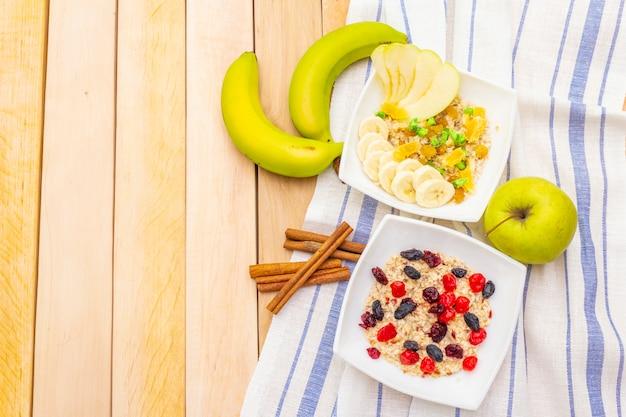 オートミールとフルーツを含む健康的なベジタリアン(ビーガン)朝食。木製テーブル