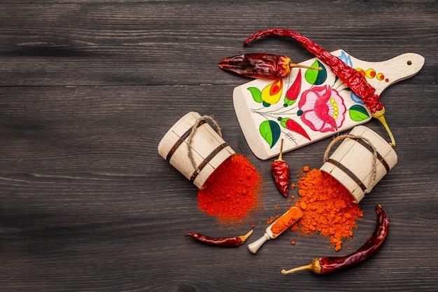 マジャールレッドの甘くて熱いパプリカパウダー。まな板の伝統的なパターン、乾いたコショウのさまざまな品種。ブラック木製