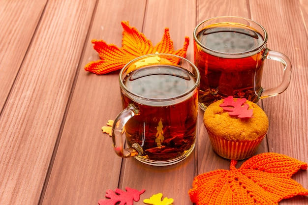 Горячий осенний напиток. черный чай с кексами, разноцветными листьями