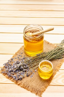 木製の蜂蜜ディッパーとガラスの瓶に新鮮な液体蜂蜜