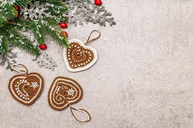 クリスマスの背景。新年のモミの木、犬のバラ、新鮮な葉、かぎ針編みのジンジャークッキーの心、人工雪。