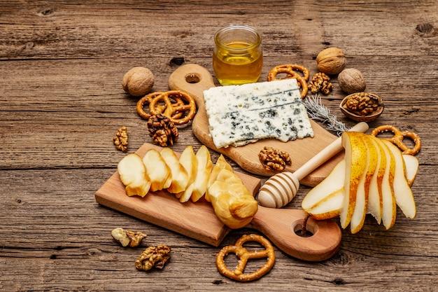 スモークチーズとブルーチーズ、クラッカー、蜂蜜、クルミ、熟した洋ナシのチーズプレート前菜