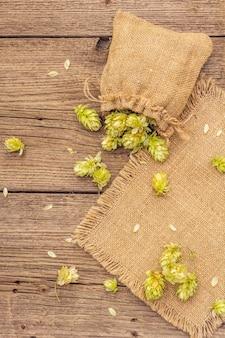 木製の古いテーブルの上にバッグのホップ全体。醸造所。ビール成分。ビンテージボードのホップの袋