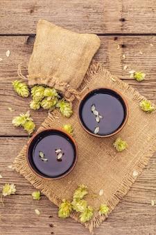 Чашка успокаивающего травяного чая со свежим диким хмелем. шишки хмеля в мешке на старинных досках