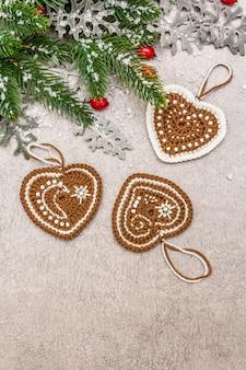Новогодняя елка, шиповник, свежие листья, вязаные имбирные печенья сердечки и искусственный снег.
