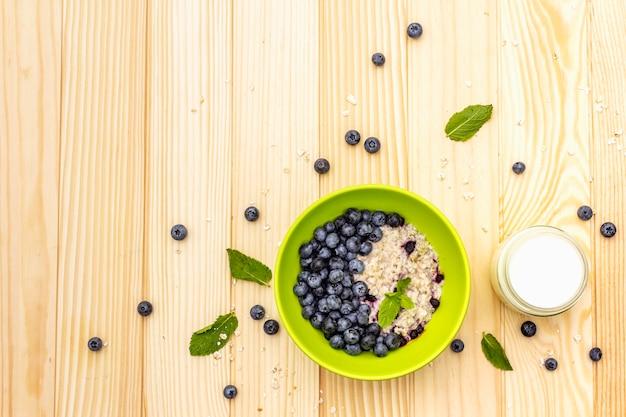 Овсяная каша со свежей черникой, листьями мяты и йогуртом
