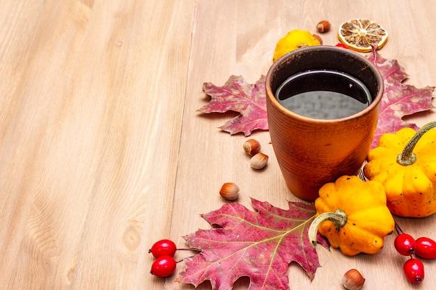 Осеннее уютное настроение композиции. горячий чай в керамическом стакане, осенние листья, тыквы, шиповник, фундук