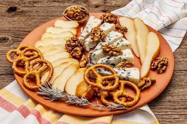 Сырная тарелка антипасти с копченым и голубым сыром, крекерами, медом, грецкими орехами и спелой грушей