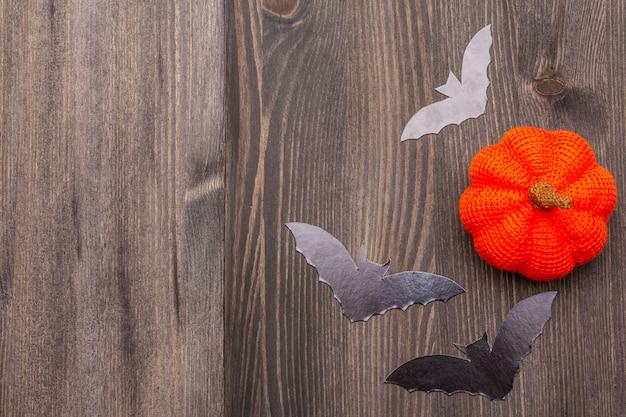 Концепция украшения хэллоуина - черные летучие мыши и оранжевые тыквы на темном деревянном фоне