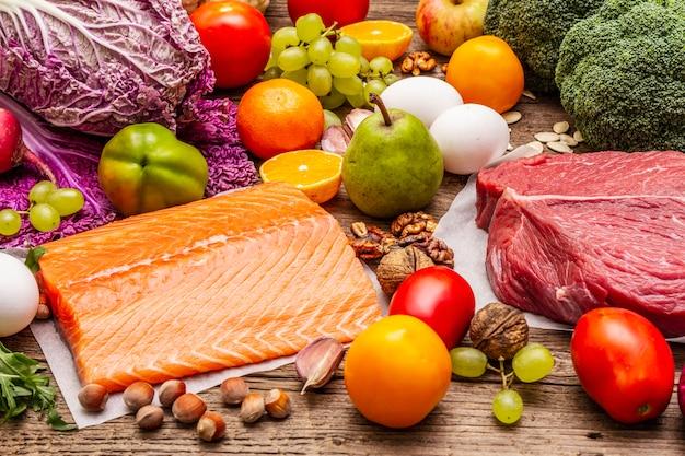 流行の古食/ペガン食。健康的なバランスのとれた食品のコンセプト。生鮮食品、生肉、サーモン、野菜、果物のセット