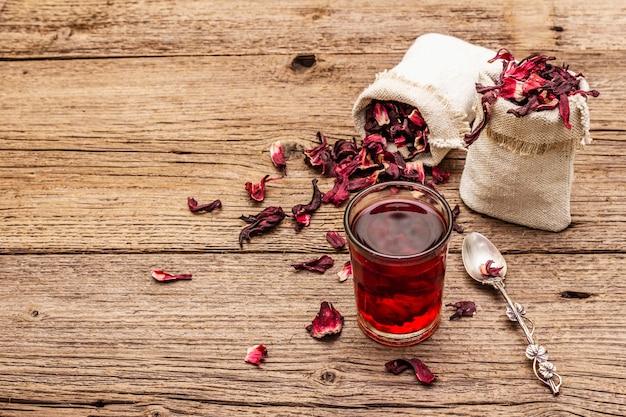 ホットハイビスカスティー。乾燥した花びら、リネン袋。健康食品とセルフケアのコンセプト。