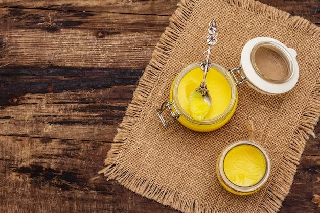 ピュアまたはデジギー(ギ)、透明な溶けたバター。健康的な脂肪防弾ダイエットコンセプトまたは古スタイルの計画。ガラスの瓶、ヴィンテージ荒布を着た銀のスプーン。