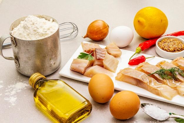 Сырое филе трески с овощами, специями, яйцами, оливковым маслом и мукой