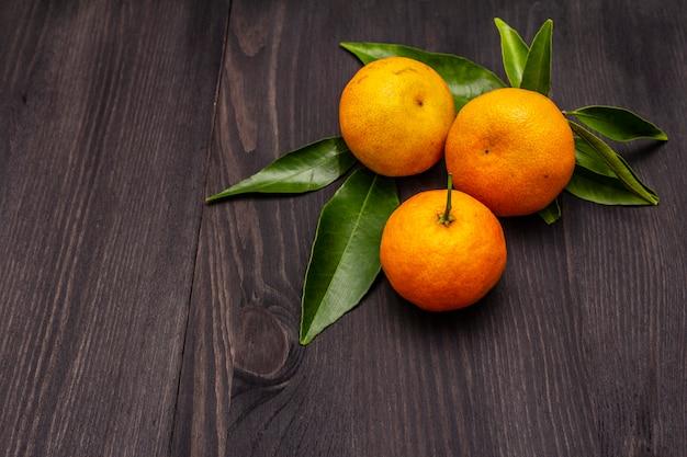 Свежие спелые мандарины с листьями на деревянный стол