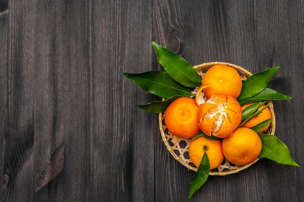 Свежие спелые мандарины с листьями в корзине.