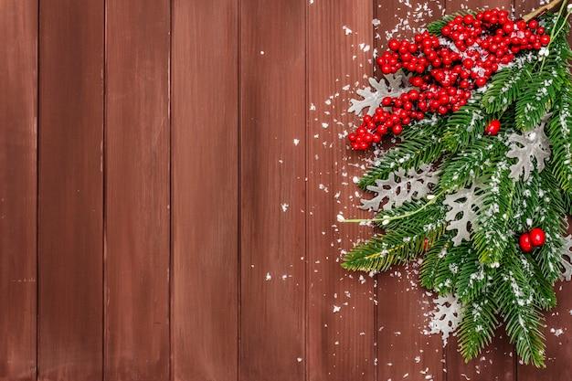クリスマスの背景。新年のモミの木、犬のバラ、新鮮な葉、人工雪。
