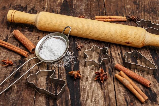 クリスマスのベーキング、焼き物、スパイス、クッキーカッター-星、天使とモミの木、ふるい、砂糖の粉、麺棒。古い木の板