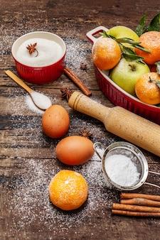 クリスマスベーキングを調理するための原料。ヴィンテージの木製テーブル