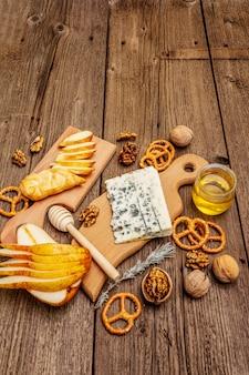 スモークチーズとブルーチーズ、クラッカー、蜂蜜、クルミ、熟した洋ナシのチーズプレート前菜。伝統的なスナックのレシピ