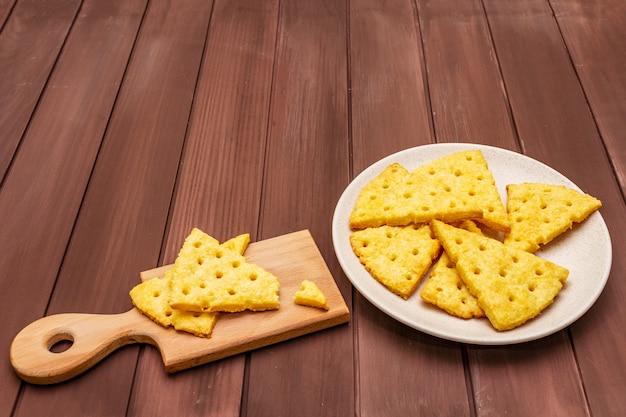 チーズクラッカー、塩味のスナックコンセプト。クッキー、プレート、まな板。