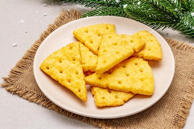 お祝いチーズクラッカー、新年のおやつコンセプト。クッキー、モミの木の枝、人工雪、荒布ナプキン。石のコンクリートの背景