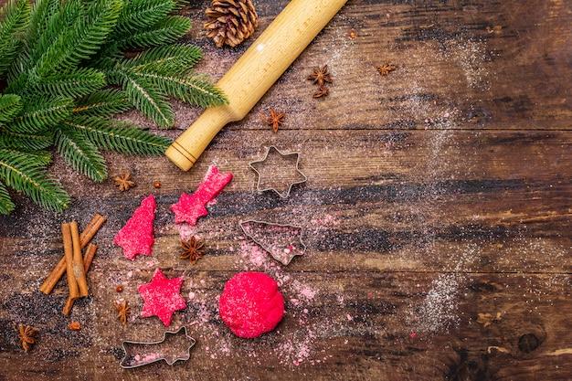 Приготовление красного имбирного печенья. традиционная рождественская выпечка. ель, специи, формочки для печенья, сырое тесто, скалка, деревянные доски