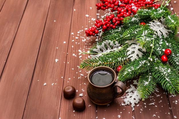 クリスマスホットコーヒーの背景。新年のモミの木、犬のバラ、新鮮な葉、チョコレート菓子、人工雪。