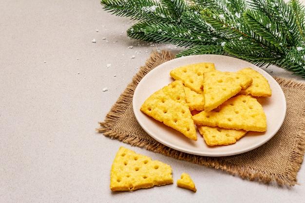お祝いチーズクラッカー、新年のおやつコンセプト。クッキー、モミの木の枝、人工雪、荒布ナプキン。