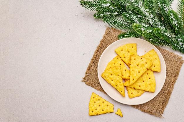 Праздничный сыр крекеры, концепция закуски новый год. печенье, ветка ели, искусственный снег, вретище салфетка.