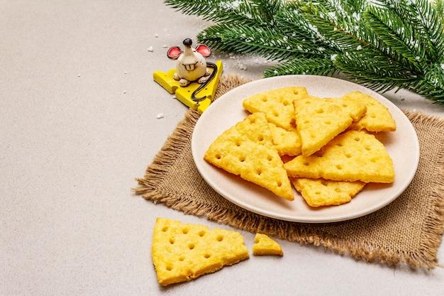 お祝いチーズクラッカー、新年のおやつコンセプト。クッキー、マウスフィギュア、モミの木の枝、人工雪、荒布ナプキン。