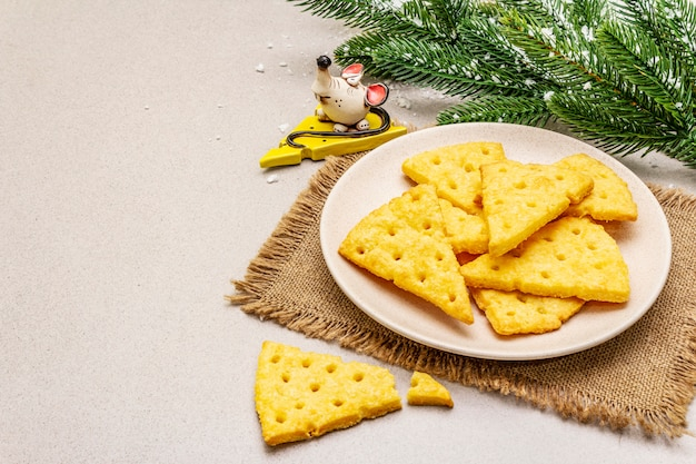 Праздничный сыр крекеры, концепция закуски новый год. печенье, фигурка мыши, ветка ели, искусственный снег, вретище салфетка.