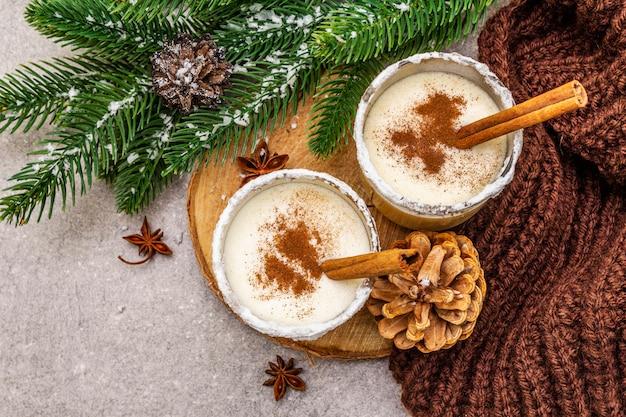 ガラスにシナモンと自家製エッグノッグ。典型的なクリスマスデザート。常緑のモミのブランチ、コーン、居心地の良い格子縞、人工雪。