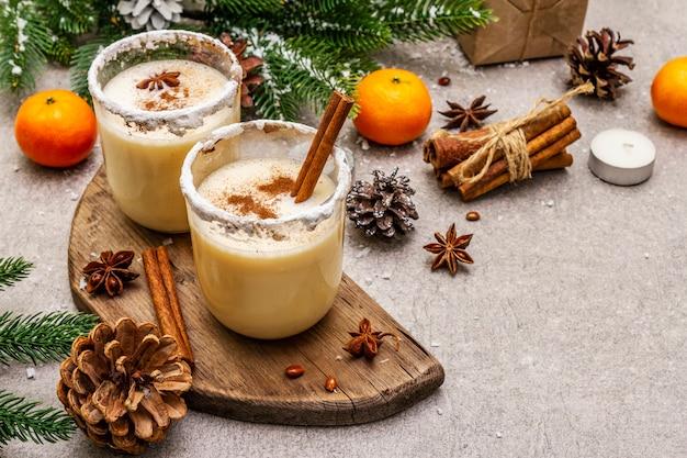 クリスマスと冬休みにシナモンとナツメグのエッグノッグ。スパイシーな縁のあるグラスに自家製の飲み物。みかん、キャンドル、ギフト。