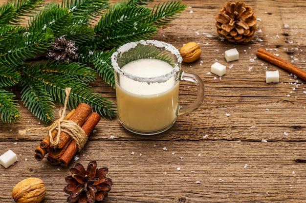 クリスマスエッグノッグリキュールまたはコーラデモノカクテル。ガラスマグカップ、クリスマスデコレーションの古典的な冬の飲み物。常緑の枝、シナモン、クルミ、砂糖。