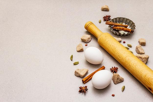 スパイス、卵、茶色の塊の砂糖、カップケーキのグラタン皿、麺棒。光