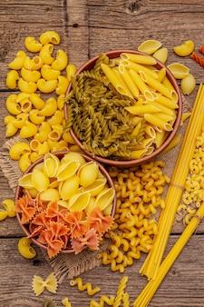 Разные виды макарон в керамических мисках. традиционная итальянская еда, концепция здорового питания. деревенский деревянный стол