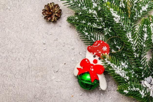 クリスマスの飾り。常緑のモミの木の枝、コーン、雪だるま、人工雪。