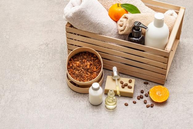 Концепция спа кофе и мандарина. полотенца, масло, скраб, мыло, лосьон. натуральный ингредиент, деревянная коробка.