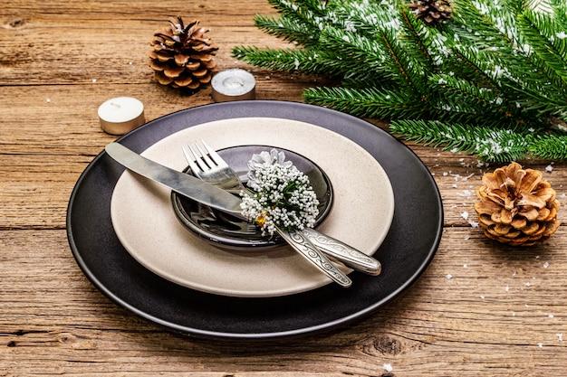 クリスマスと新年のディナーの場所の設定。常緑のモミの木の枝、キャンドル、コーン、セラミックプレート、フォーク、ナイフ。