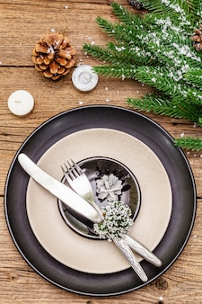 Урегулирование рождественского и новогоднего ужина вечнозеленая еловая ветка, свечи, шишки, керамические тарелки, вилка и нож.