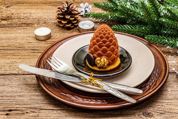 Урегулирование рождественского и новогоднего ужина сладкие закуски, ветка ели, свечи, шишки, керамические тарелки, вилка и нож.