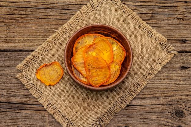 Сушеные ломтики хурмы в миску. фруктовая закуска, концепция здорового питания