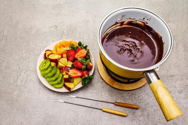 Шоколадное фондю. ассорти из свежих фруктов, два вида шоколада. ингредиенты для приготовления сладкого романтического десерта.