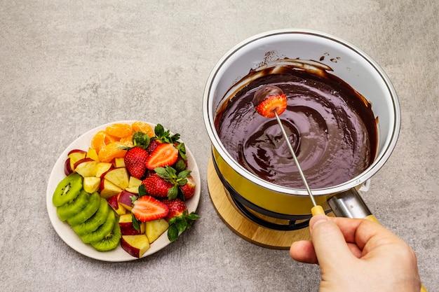 Шоколадное фондю. ассорти из свежих фруктов, два вида шоколада, мужская рука. ингредиенты для приготовления сладкого романтического десерта.