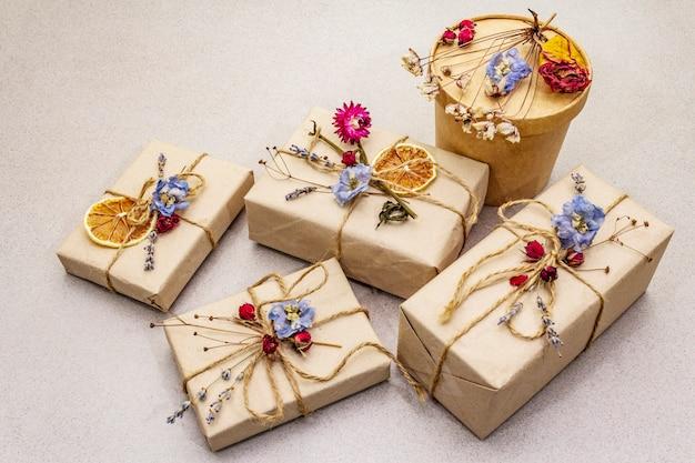 廃棄物ゼロギフトコンセプト。誕生日に優しいパッケージ。さまざまな有機装飾が施されたクラフト紙のお祝いボックス。